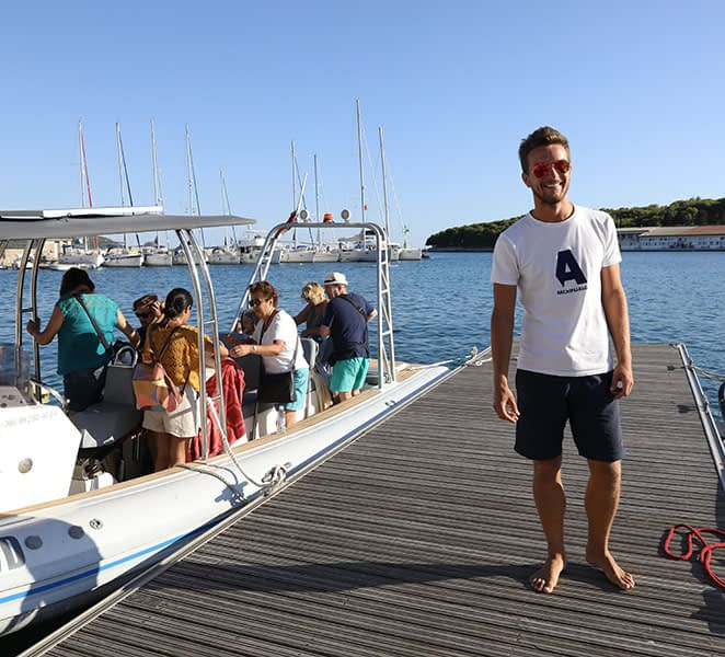Archipelago Tours - About us - photo of the skipper/guide with the boat and tourists in Prvic Luka on island Prvic