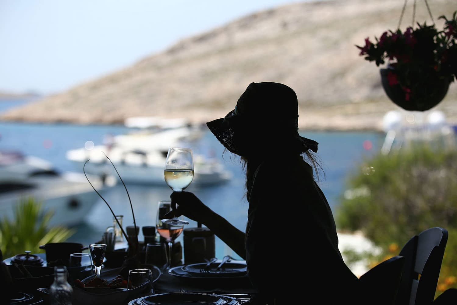 Archipelago Tours Custom Made Tours Exclusive Charter photo of a women holding wine glass with boats and sea in the background