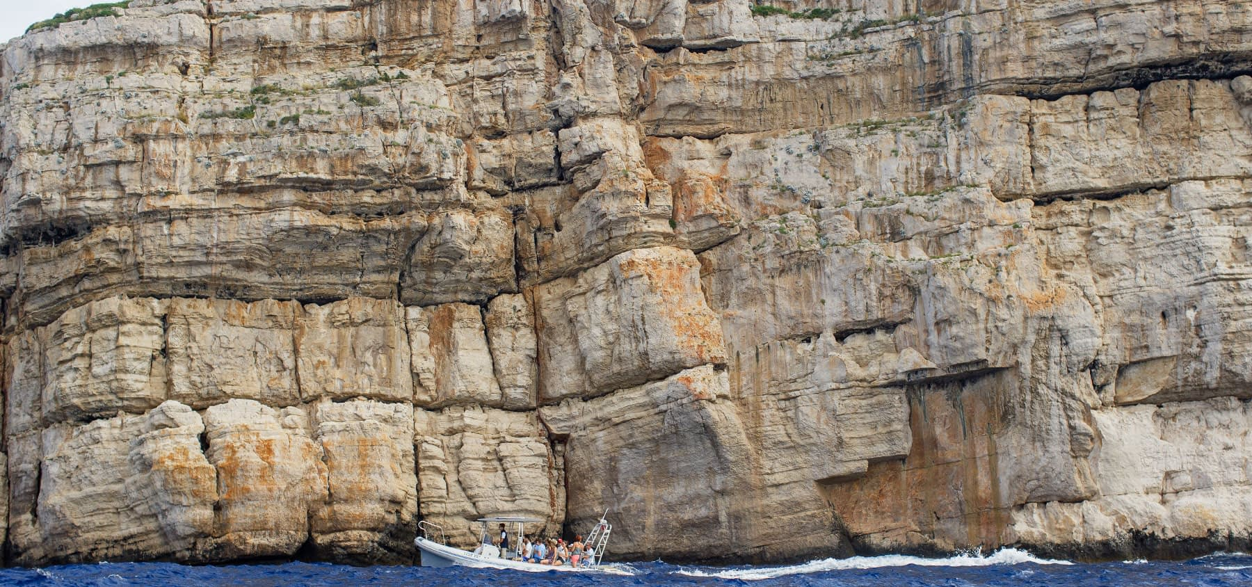 Archipelago Tours Blog and Tips: Carved by the elements - photo of our boat under one of the cliffs in Kornati archipelago