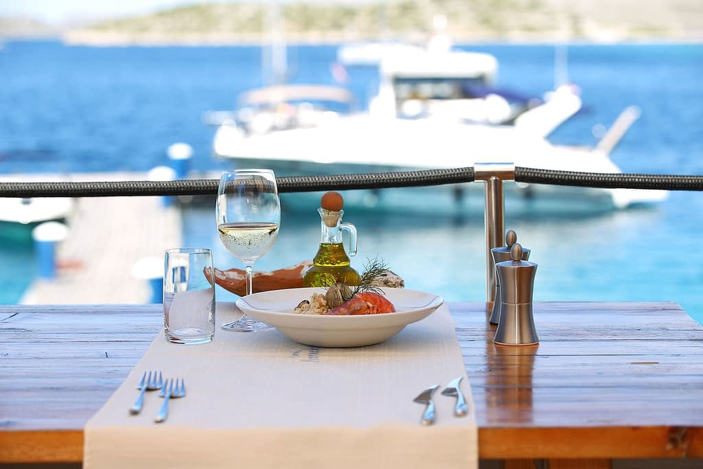 Archipelago Tours Kornati Experience Small Group Tour photo of table with glass of wine and a plate with risotto with boats and the sea in the background