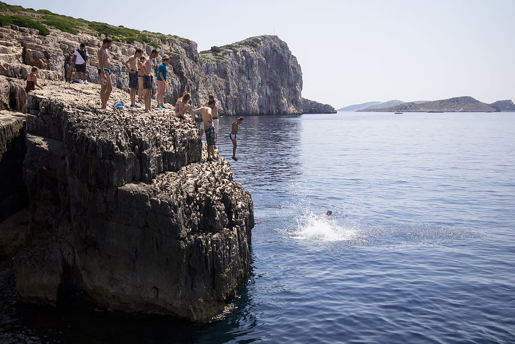 Archipelago Tours Kornati Experience Small Group Tour photo of tourist taking a dive from a cliff on Mana island in Kornati national park