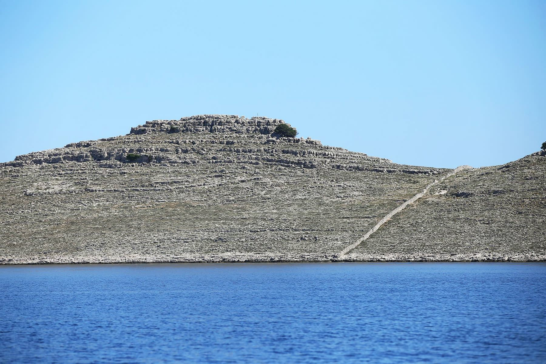 Archipelago Tours Photo showing a detail of one island in Kornati intersected by stonewall